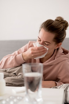 Woman blowing her nose and being indoors