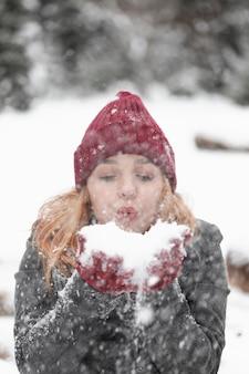 Женщина дует в кучу снега вид спереди