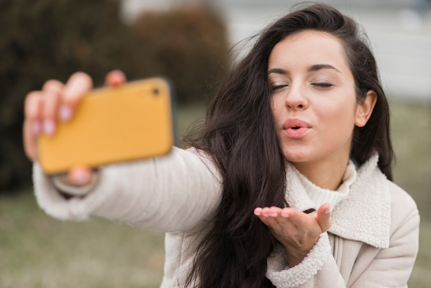 Woman blowing kiss while taking selfie