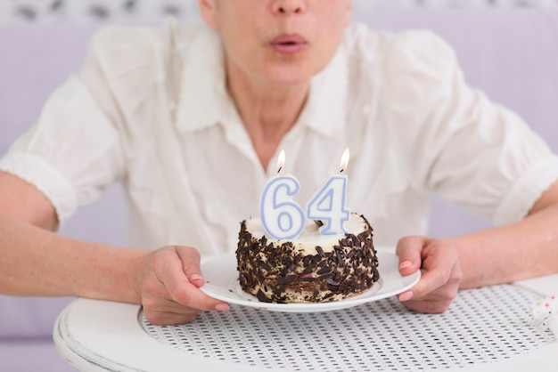 Woman blowing number candles over her birthday cake on table