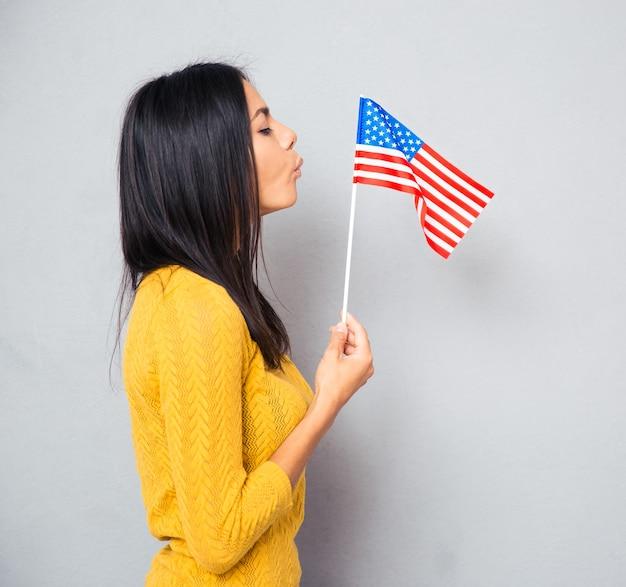 Женщина дует на американский флаг