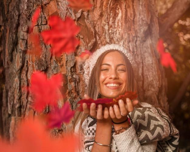 Женщина дует на осенние листья и смеется