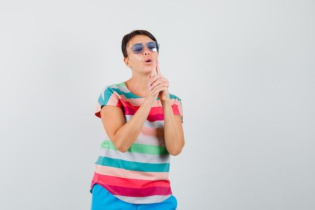 Женщина дует в пистолет на палец в полосатой футболке, штанах и выглядит уверенно