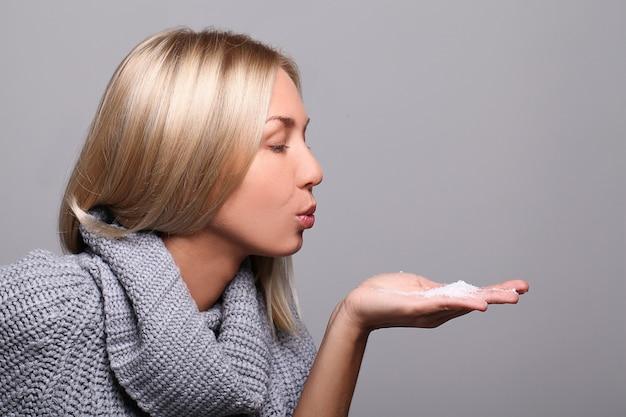 Donna che soffia fiocchi di neve dalla sua mano