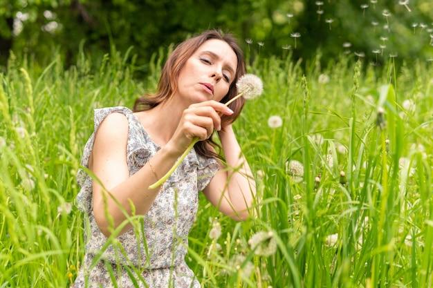 女性は自然の中でタンポポを吹いて公園を歩く