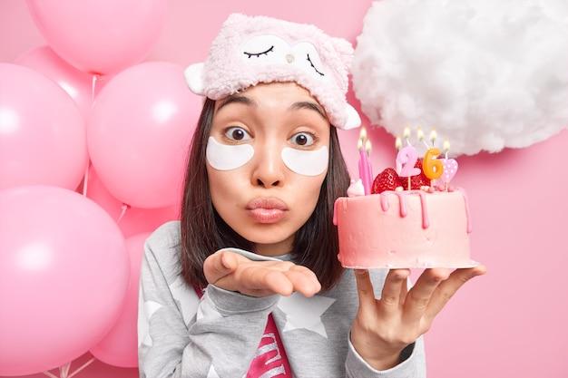 La donna soffia aria bacio alla telecamera tiene le labbra piegate tiene la torta festiva con candele accese si prepara per le celebrazioni applica cerotti di bellezza
