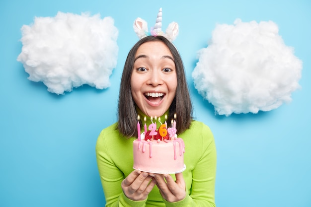 Woman blows candles on birthday cake wears unicorn headband makes wish has happy festive mood isolated on blue