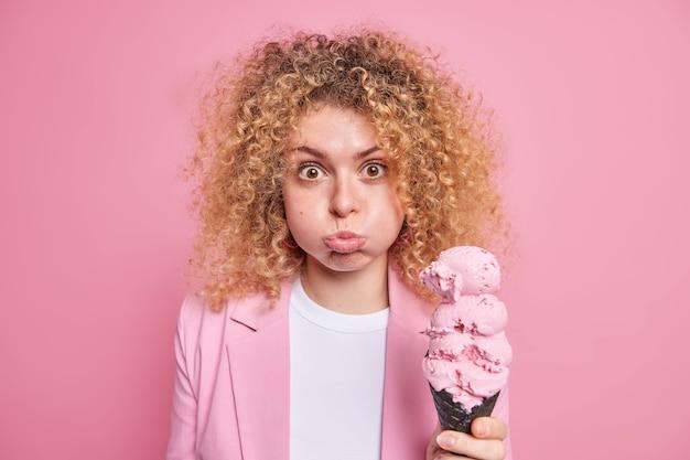 여자가 뺨을 불면 웃긴 얼굴을 하고 크고 맛있는 냉동 아이스크림을 들고 분홍색으로 공식적으로 격리된 옷을 입고 여름 디저트를 즐긴다