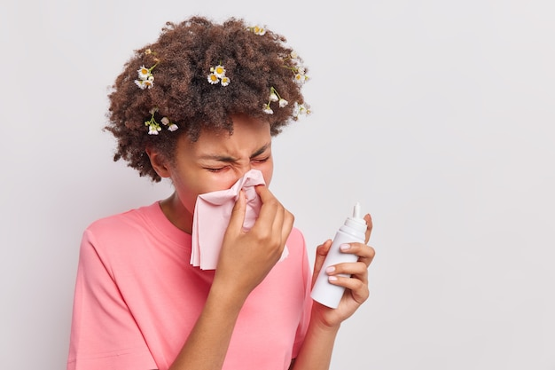 여자는 티슈 스프레이로 코를 풀고 알레르기 반응을 일으키며 흰색으로 격리된 캐주얼한 분홍색 티셔츠를 입는다