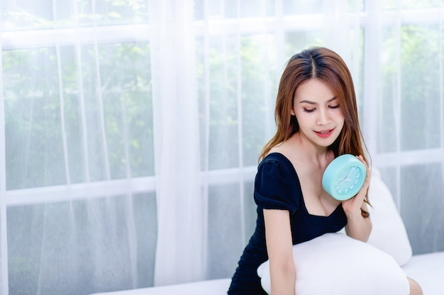 Woman and blue alarm clock in the bedroom relaxation concept
