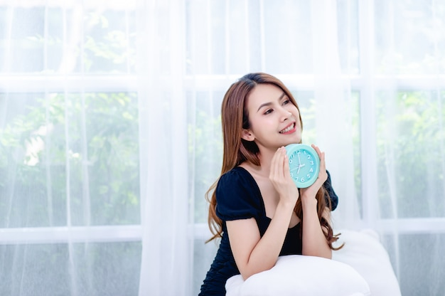 Woman and blue alarm clock in the bedroom relaxation