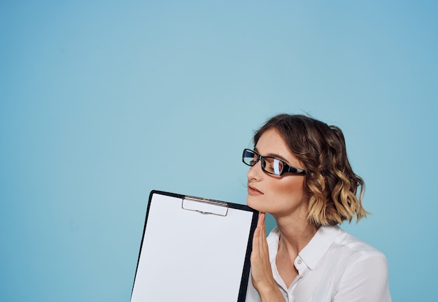 Woman on a blue background with a folder of documents in the hands of a white sheet of mockup paper
