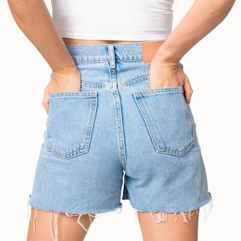 Donna in pantaloncini di jeans blu con la mano infilata nella tasca vista posteriore