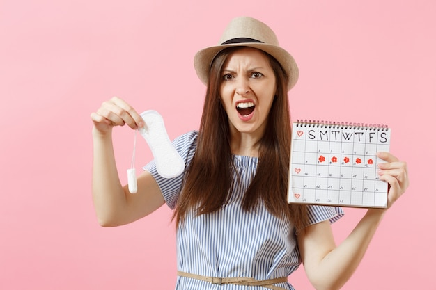 Woman in blue dress, hat holding sanitary napkin, tampon female periods calendar, checking menstruation days isolated on pink background. medical, healthcare, gynecological choice concept. copy space.
