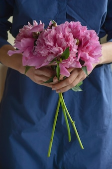 Woman in blue dress holding pink pions peonies flowers. close up
