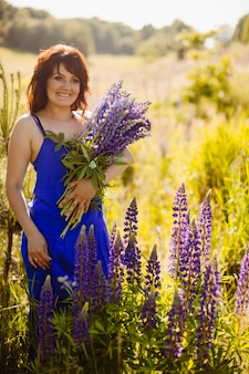 Woman in blue dress poses with bouquet of lavander on the field