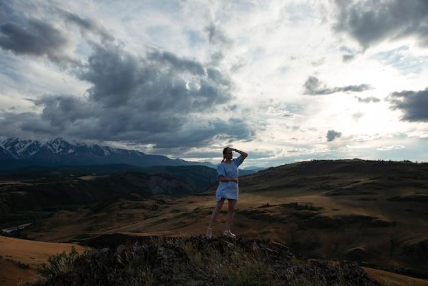 Woman in blue dress in summer altai mountains in kurai steppe