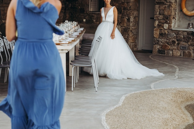 Woman in blue dress walks towards the bride in classy wedding gown