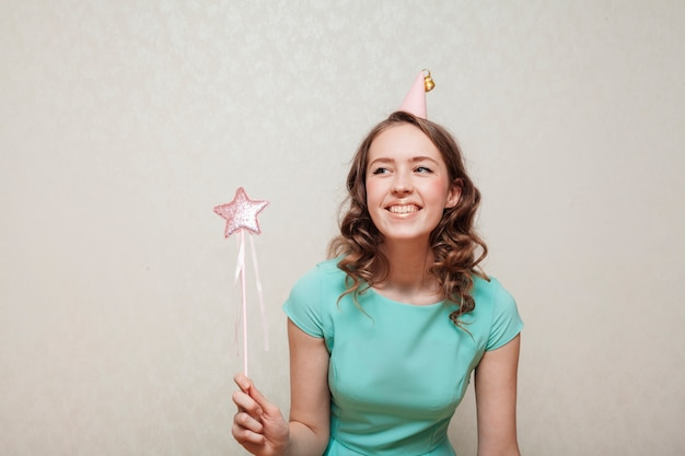 Woman in blue dress wearing a party hat and looking away