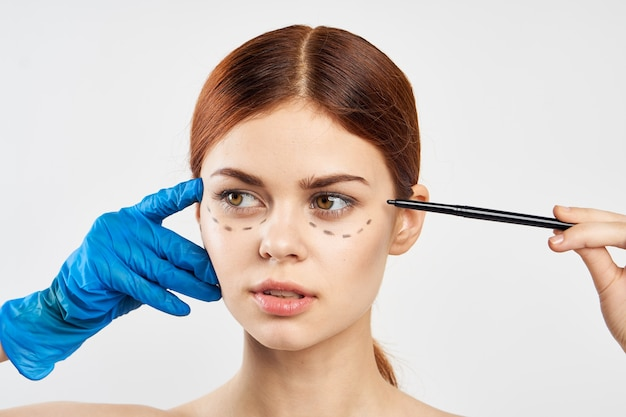 A woman in blue gloves holds a syringe in her hands and points botox injection operation on her face