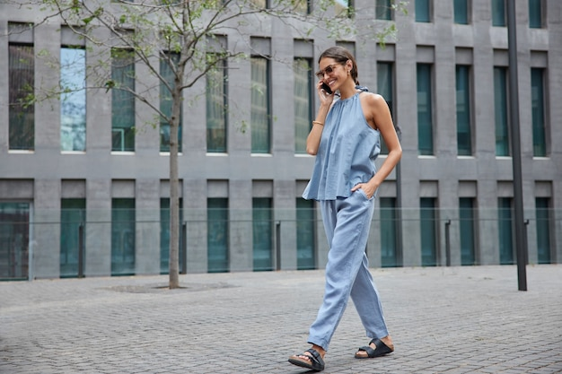 Woman in blue outfit enjoys cellphone conversation in roaming while traveling abroad makes smartphone calling via app strolls outdoor near modern establishment