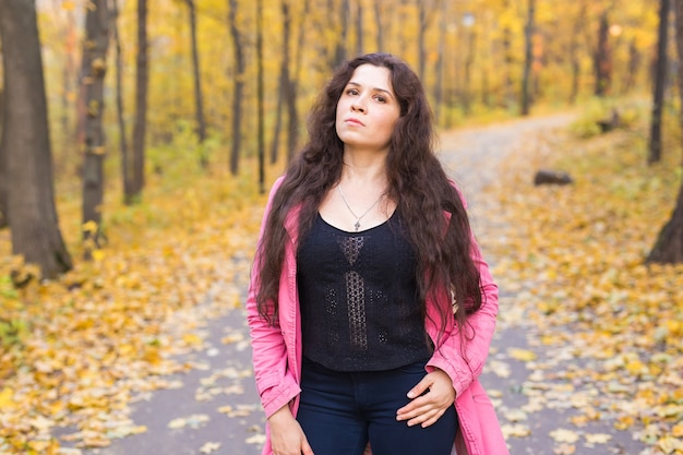 Woman in blue pants and pink jacket standing in autumn forest