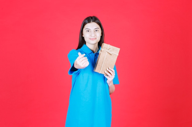 Woman in blue shirt holding a cardboard mini gift box and doing finger heart gesture