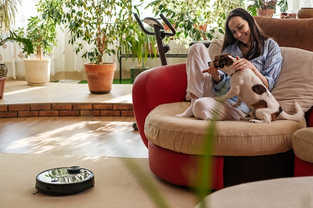 Woman in blue shirt plays with dog, jack russell terrier breed at home on couch, robotic vacuum cleaner on carpet