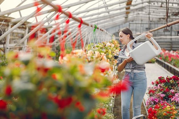 Woman in a blue shirt pours flowerpots