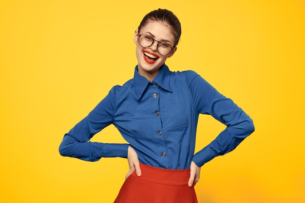 Woman in blue shirt and red skirt glasses on face confident look portrait yellow wall cropped view.