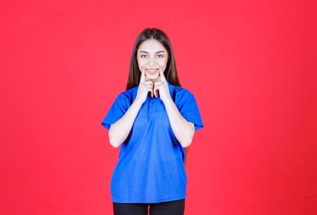 Donna in camicia blu in piedi sul muro rosso.