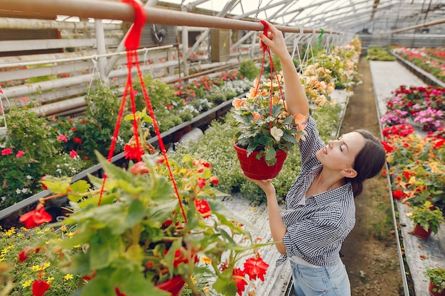 Woman in a blue shirt working in a greenhouse