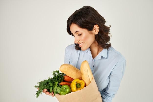 女性の青いシャツパッケージ野菜食料品の配達
