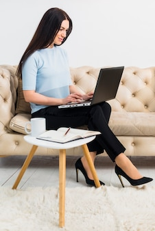 Woman in blue sitting on couch with laptop