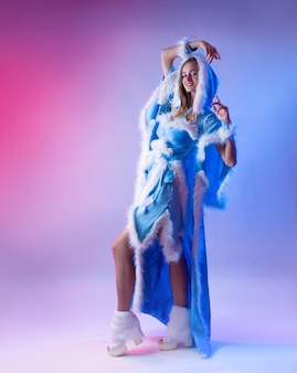 A woman in a blue snow maiden costume poses on a light neon background