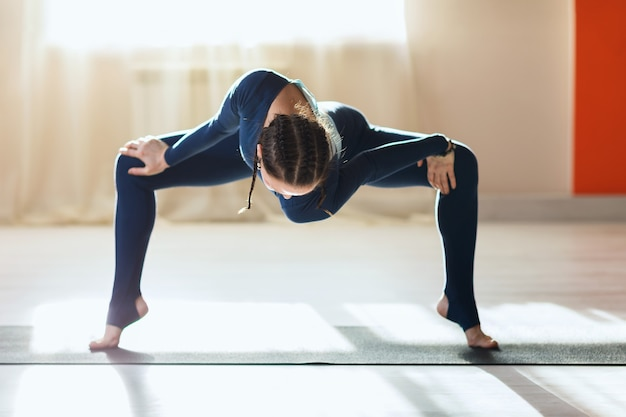 A woman in blue sportswear practicing yoga performs twisting in rudrasana in an apartment near the window