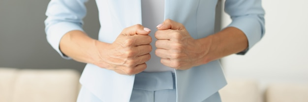 Woman in blue suit holding edges of her jacket with her hands closeup