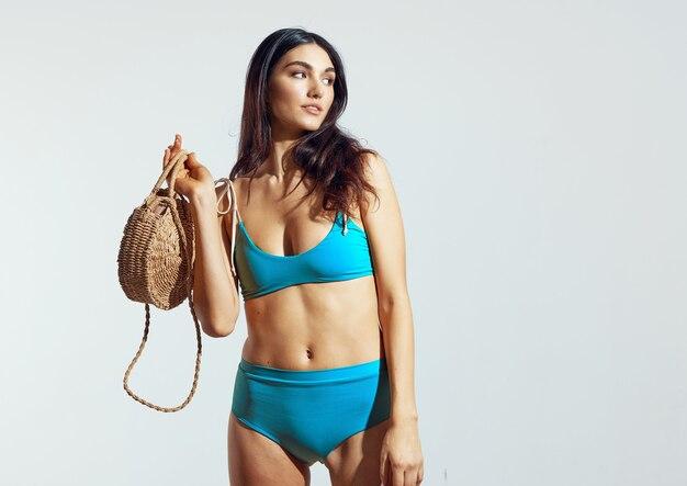 Женщина синий купальники пляжная сумка позирует бикини летом