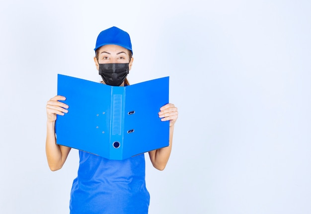 Woman in blue uniform and black face mask opening a blue folder and checking it.