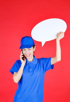 Woman in blue uniform holding an ovale idea board and talking to the phone.