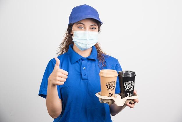 Donna in uniforme blu con maschera medica che tiene due tazze di caffè e mostra un gesto ok su bianco