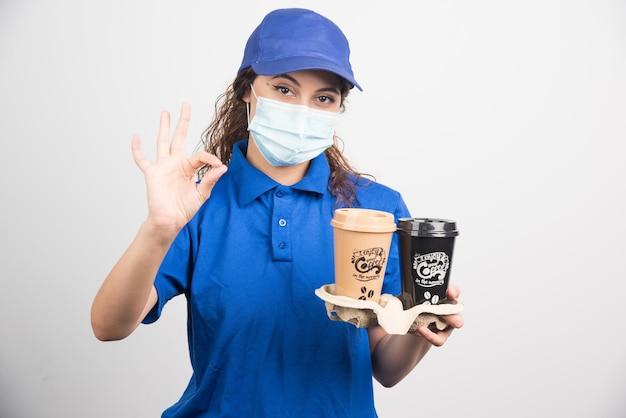 Donna in uniforme blu con maschera medica che tiene due tazze di caffè e mostra il pollice su bianco