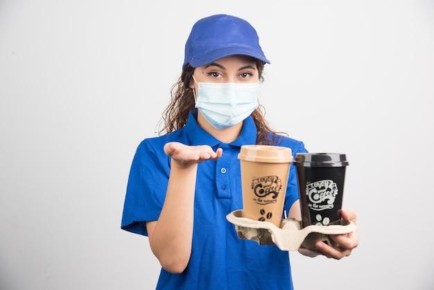 Donna in uniforme blu con maschera medica che tiene due tazze di caffè su bianco