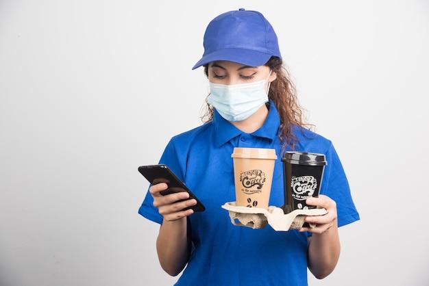 Donna in uniforme blu con maschera medica che guarda al telefono e tiene in mano due tazze di caffè su bianco