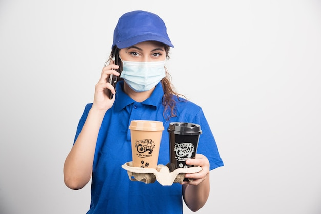 Donna in uniforme blu con maschera medica che parla al telefono e tiene in mano due tazze di caffè su bianco