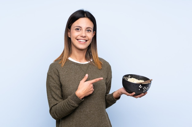 Woman over blue wall and pointing it while holding a bowl of noodles with chopsticks