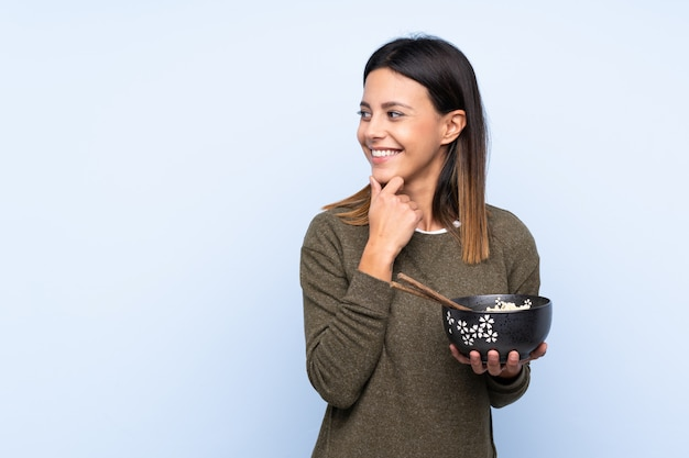 Woman over blue wall thinking an idea and looking side while holding a bowl of noodles with chopsticks