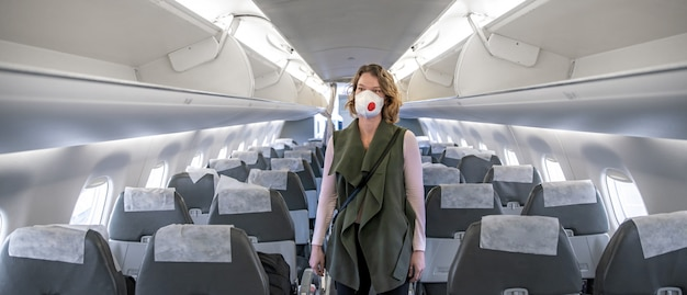 Woman on board of aircraft with respirator on head.
