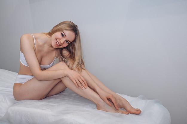 完璧な滑らかな柔らかい肌のペディキュアで日焼けした長い脚を持つ女性のボディケア美しい金髪の女性
