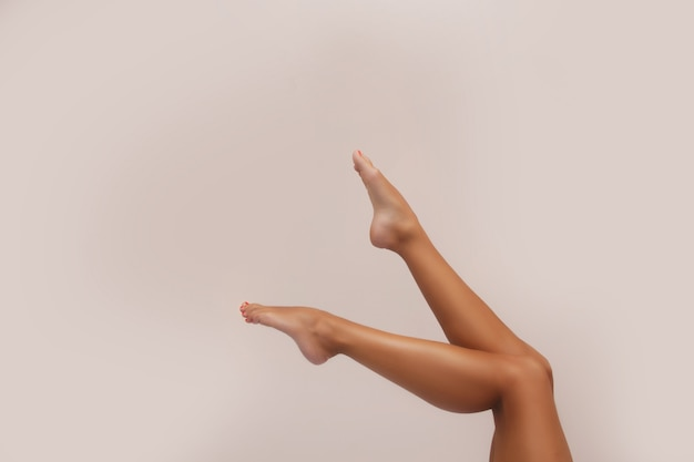 Woman body care. close up of long female tanned legs with perfect smooth soft skin, pedicure. epilation, beauty and health concept